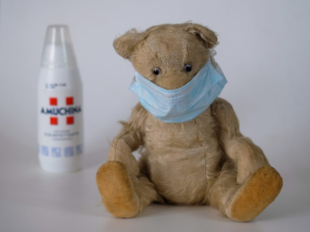 Teddy bear wearing face mask with sanitiser in the background. Summary for the article '7 Marketing Projects to Keep You Productive During Quarantine' by Hana Clode Marketing.